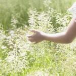 journal writing - shown by girl running hand through tall grass