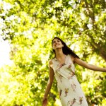 meditation for relaxation shown by happy woman standing with arms stretched out