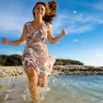 how to achieve exercise goals - woman running on beach!