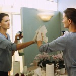 Spring Clean Your Life shown by woman cleaning mirror