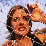 Woman Confined Behind a Chain-Link Fence